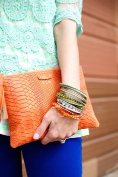 Teal blouse, orange clutch and stacked bracelets :)