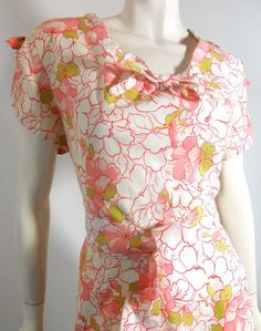 "Crisp cotton 1950s hand made summer dress in white with pink and chartreuse floral print. Skinny side metal zip, notched sleeves with bows, wide sash. No flaws.   Measures 38"" bust, 29"" waist, 44"" hips, 17"" bodice, 42"" long"