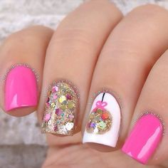 Colorful and pretty glitter nail art details on top of white and pink matte polishes.