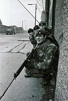 Northern Irish children take cover behind a British Army trooper during The Troubles, Belfast, Northern Ireland, British Armed Forces, British Soldier, British Army, Northern Ireland Troubles, Irish Republican Army, War Photography, Street Photography, Falklands War, Northern Irish