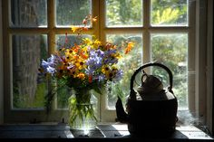 Cozy scene with sunlit flowers, kettle, and cobwebs. I picture tidying the place up to look as lovely and welcoming as the arrangement. Heligan by Jon Iles, via Flickr