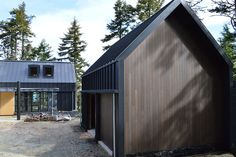 The garage exhibits the same black steel cladding and stained cedar siding as the main structure. Flat dormer windows on the house provide natural light and add visual interest to the overall shape.