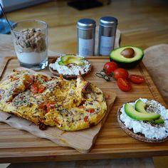 Frühstücks-Kombi: Omelette mit Tomaten und Zwiebeln, zwei Vollkorn-Toasties mit körnigem Frischkäse und Avocado sowie Joghurt mit Dinkel-Crunch-Müsli.