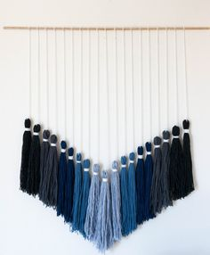 The Rigby Tassel Tapestry is handmade with various shades of blues and grays with ivory yarn. The ombre effect adds a special touch to the piece. This unique tapestry will instantly dress up a space and add a personal touch to any room. This piece is made-to-order, which means you can choose any colors youd like! They could all be the same color story (blues or reds or greens) or a combination of 5 different colors - you choose! ------------------------------------ This tassel tapestry…