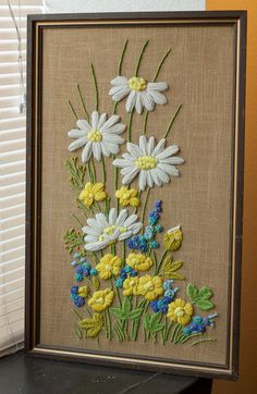 """Bright and cheery embroidered flowers in white, yellow, blue & green yarn, on a tan burlap background."" From Tarragon Vintage on etsy."