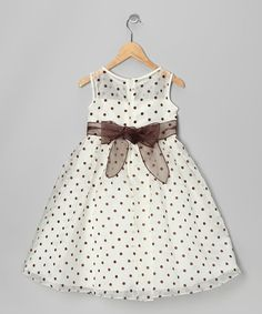 Whether helping to host the big soiree or simply practicing the bunny hop, any little reveler will charm one and all decked out in this party-ready piece with its sweeping skirt, mesmerizing print and generous floral accent.