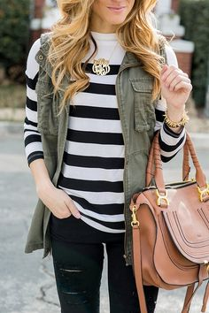 olive green utility vest with black and white striped tee