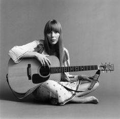 Portrait of American musician Joni Mitchell seated on the floor with her acoustic guitar in her lap. Description from gettyimages.com. I searched for this on bing.com/images
