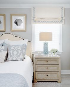 An elegant bedroom in soft blues designed by Leedy Interiors features a neutral linen roman shade with Ogee Embroidered Border from Samuel & Sons