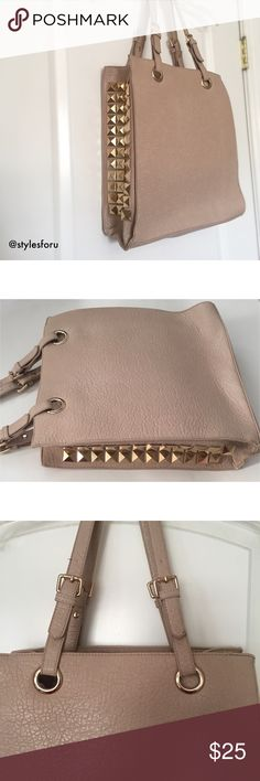 """NWT. Tan side studded tote NWT. Tan side studded tote. Size: 14"""" x 12.75"""" x 5"""" (can fit books, a laptop, etc.) Adjustable shoulder straps. Gold metal details. Faux leather. 2 inside compartment pockets and a zipper pocket. Sorry, no trades. Like the item but not the price, feel free to make me a reasonable offer using the offer button. Bag Haven Bags Totes"""