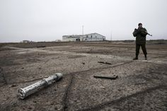 An armed man with the separatist self-proclaimed Donetsk People's Republic army stands near the remnants of a cluster bomb container at the Donetsk airport, February 26, 2015. REUTERS/Baz Ratner