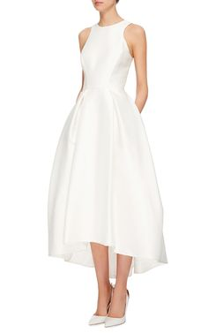 This silk Mikado **Monique Lhuillier** dress features a jewel neck with a racer design at the shoulders, a fitted bodice with pleats at the hips, and a midi length asymmetric a-line skirt.