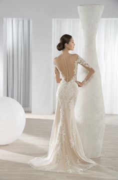 Lace sheath gown with low, sheer back with button closures and Chapel train. #DemetriosBride Style 635.