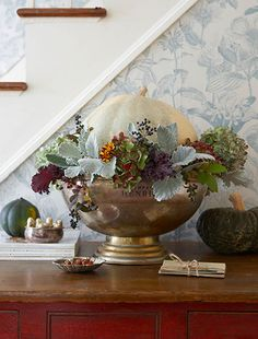 A white pumpkin sits in a pewter punch bowl surrounded by summer hydrangeas, lambs ear, leaves of huechera and the last of summer marigolds. Design by Karin Lidbeck Brent, Photography by Michael Partenio