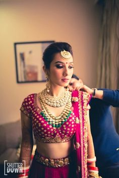 deep maroon bridal lehenga , contrast jewellery , emerald and polki necklace , ruby pink bridal lehenga ,magenta blouse , maang tikka , polki necklace