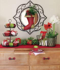 This Christmas buffet features an array of Willow House wonder. Our Holiday Door Bucket centered on our iron Medallion Mirror sets the holiday theme. To the left, our ever popular and versatile French Wire Tiered Stand holds fruits, small gifts and candies served in Cinnabar Tidbits. On the right, small gifts are tucked inside a French Wire Convertible Basket and a French Wire Plant Holder holds beautiful flowers that add color and height to the grouping. The place setting layers a Cinnabar…