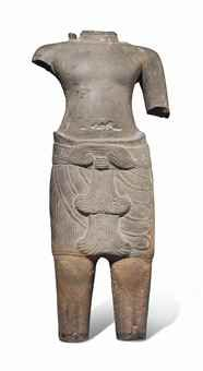 A SANDSTONE MALE TORSO CAMBODIA, KHMER, ANGKOR WAT PERIOD, 12TH CENTURY Carved standing, wearing a striated sampot secured with a belt and a double fish-tailed sash falling to the front, the reverse with butterfly-shaped knot around the waist, with bare chest 19 ¾ in. (50 cm.) high