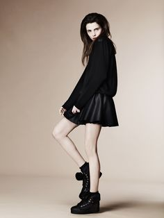 Pale, dark hair, black blouse, bare legs and big shoes.