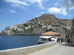 We were walking back to the main port on the island of Hydra,Greece..after swimming at the small beach at Avlaki. This coastal road rises in elevation..so we had to walk down 78 steps to reach the swimming area. It was worth it. The Aegean Sea was warm and clear. The port is crescent shaped..and the view in the background is what all visitors see upon boat arrival from Athens.
