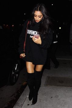 Shay Mitchell wearing Stuart Weitzman Highland Boots, Givenchy Destroyed Sweatshirt, Chanel Flap Bag with Top Handle and Milkyway Flamingo Floaties Clear Iphone Case
