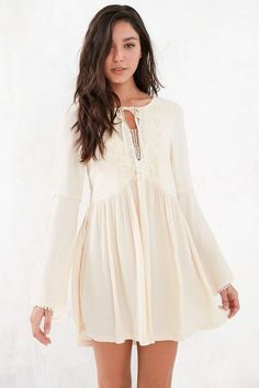 Floaty bell-sleeve frock dress from boho label Kiss the Sky.  With a tie-front chest + applique trim, finished with cut outs at the shoulders and a drapey, dropp
