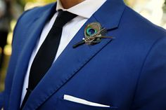 much better composition. clean suit, simple black tie, ironed white pocket square, peacock boutonniere