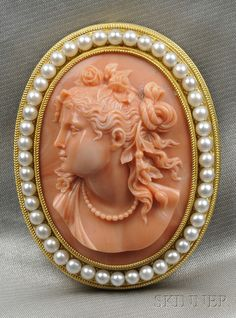 High-Karat Gold, Coral Cameo, and Cultured Pearl Brooch, the cameo depicting a maiden with flowing hair and flowers, cultured pearl border, and fine braided gold frame, 2 1/4 x 1 3/4 in.