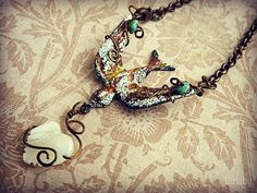 Sweet bird pendant with rust and patina, carrying a mother of pearl heart. Rusty black heart from B'Sue Boutiques
