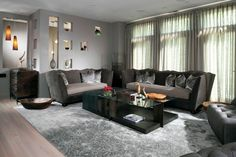 This living room strives for a unique look, with deep grey tones on the walls, furniture, and patterned area rug in lieu of the popular off-white styles. The walls are pocked with display cutouts for displaying art, while both a rustic dresser and ultra-modern glass table share the room.