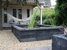 Een hele strakke vijver in een minimalistische tuin de klant