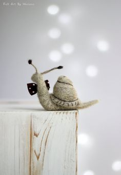 This little needle felted Snail was born in Sofia a few days ago. But already has his own style he is made of wool and has brown tie. Size in centimeters: 9 cm long  Size in inches: 3.5 long  He is little but is not afraid of birds.  I use felt needle techniques and 100% pure wool form Bulgaria. I dye the wool by myself to achieve the right colors.  I love to make little dolls and hope you like them too.  https://www.facebook.com/FeltArtByMariana
