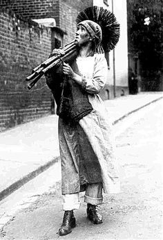 Women's War Work 1914-1918.   Mrs Rosanna Forster from Kent is a chimney sweep, carrying on her husband's business while he serves abroad. Here, she walks along a road, her brooms over her shoulder.