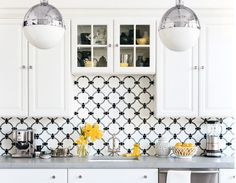 modern way If your kitchen is primarily all-white, then let the backsplash bring in the touches of color. Graphic tiles in black and gray offer just the right amount of pattern to this space.
