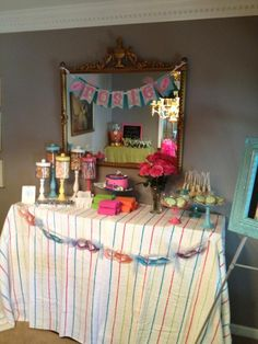Nail Polish Cake Pops, Cucumber Decorated Cookies, and Candy, with a colorful draped cloth and spa masks make this food station SPAtacular for any little girls pampering birthday party.