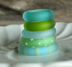 An assortment of beautiful handmade glass lampwork ring beads in soft sea glass hues. Pale aqua, soft veridian, watery teal, and celery green. Beads have been acid etched for that satin, matte appearance of sea glass. All rings handmade by me and come in a variation of sizes from 4x31mm for the largest, to 5x22mm for the smallest. The bead set comes with a FREE 24 silver-toned, (nickel plated), ball strand chain. #SB573  Hippkitty Beads, handmade by me, Vickie Miller, in my home studio of…