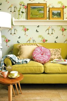 Loving the old vintage wall paper, wood plank floors, and this lovely couch.