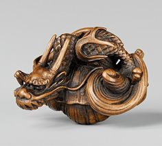An unusual wood netsuke of a dragon in a hora. First half 19th century