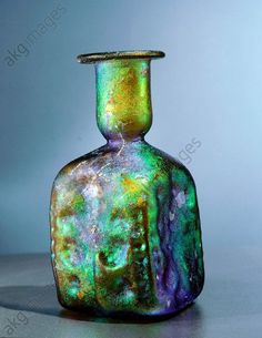 Late Roman amber glass jar with multicoloured iridescence. Mould-blown relief decorations on the square sides include a standing man with raised arms, a tree, and a date palm. Culture: Roman. Date/Per