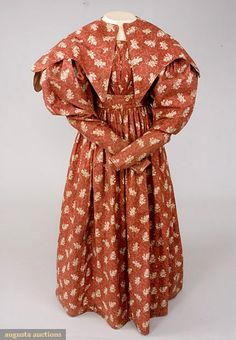 RED ROLLER PRINTED DRESS & PELERINE, 1828-1835 November, 2007 -Tasha Tudor Historic Costume Collection New Hope, PA Turkey red cotton with leaf and flower sprays and dotted stems in cream, wide scoop neckline, bodice gathered at chest in vertical pattern, full sleeves tapering to .5 cuff, upper sleeve lined with cane-inset muslin, inset waistband, full gatheredskirt, piped seams, muslin bodice lining, brown calico print cuff facings, indigo chambray hem facing, back closing, b