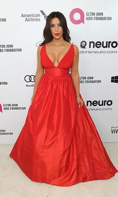 Kim Kardashian was red hot at Elton John's annual Oscars viewing party in a bright red gown.