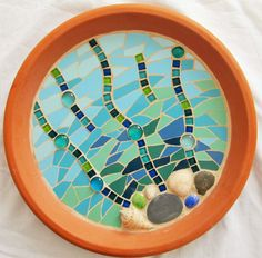 A beautiful mosaic birdbath, fully waterproofed so it is ready for the birds in your garden! This unique design is made on a terracotta base and includes a range of materials, including ceramic tiles and stone tiles. There are lots of elements which will sparkle through the water in the sunlight - the picture doesnt do it justice! All the materials used are waterproof and a special sealant is applied to protect the grout and tiles. It can be placed on top of a pedestal or on an upturned...