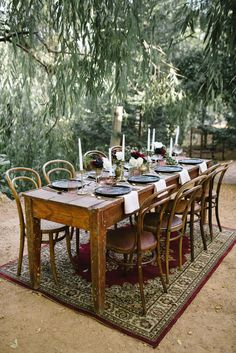 Romantic Outdoor Winery Ideas With Marsala combine a beautiful wooden table under a sweeping willow tree with black crockery and gold cutlery.