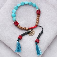 Shansta Bracelet - Bracelet with turquoise discs, silver and carved coral beads, copper and hand carved ebony wood skulls on tassels