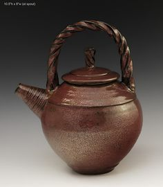 """""""Teapot #53""""  Ceramic Teapot by Ron Mello         Wheel thrown tan stoneware teapot with pulled twisted sprung handle and a rich iron red glaze. Signed on bottom."""