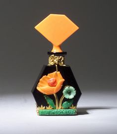 HOFFMAN perfume bottle, circa 1920s, in opaque black and orange crystal with metalwork and jewels. Metal marked CZECHOSLOVAKIA. Flaw in long jewel. Ht. 4 1/2 in (11.3 cm)     http://images.priceminer.com/images1/4/1103/01/4_c00358aaaa59222694ac9fc5de27b10e.jpg