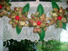 Varal de flores de tecido recheadas enfeitando a janela da casa das bonecas
