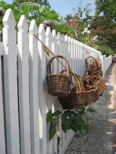 Gathering baskets on picket fence Raised Bed Fencing, White Picket Fence, Picket Fences, Brooms And Brushes, Adventures Of Tom Sawyer, Vegetable Basket, Old Fences, Fence Gate, Country Decor