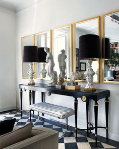 source: Nuevo Estilo  Chic black and gold living room features French black and gold console table, white and gold lamps with black linen lamp shades, gold leaf mirrors, white tufted bench with polished chrome base and black and white checkered floor.