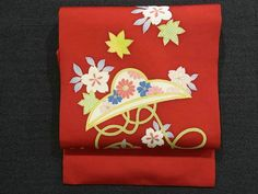 This is a Shioze Nagoya obi with a design of 'Sakura'(cherry blossom) and 'kaede'(maple leaf), which is dyed on the vibrant red background