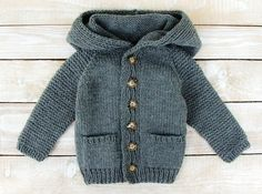 This sweater will fit baby boys up to 12 months. Hand knitted from easy care acrylic yarn, this soft gray hoodie features front pockets and an over-sized roomy hood. Would make a unique and practical new baby or shower gift. Sweater measures 13 1/2 from shoulder to hem, 11 across chest, and 12 from neckline to cuff. Machine washable.